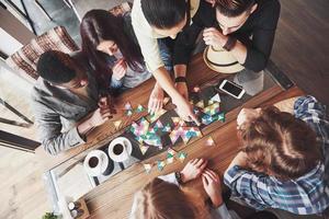 vista superior foto criativa de amigos sentados à mesa de madeira. amigos se divertindo jogando jogo de tabuleiro
