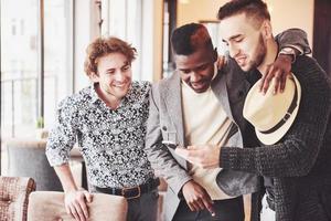velhos amigos alegres se comunicam uns com os outros e assistem ao telefone no bar. conceito de entretenimento e estilo de vida. pessoas conectadas por wi-fi em reunião de mesa de bar foto