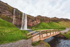 cachoeira seljalandfoss ao pôr do sol. ponte sobre o rio. natureza fantástica. Islândia. foto