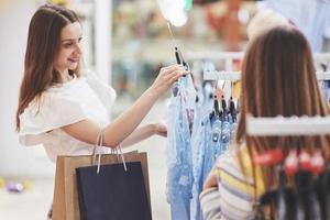 terapia de compras em ação. retrovisor de duas lindas mulheres com sacolas de compras olhando uma para a outra com um sorriso enquanto caminhava na loja de roupas foto
