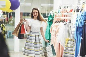 mulher nas compras. mulher feliz com sacolas de compras, desfrutando de compras. consumismo, compras, conceito de estilo de vida foto
