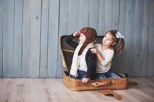 criança feliz com chapéu de piloto e menina brincando com a mala velha. infância. fantasia, imaginação. conceito de viagens foto