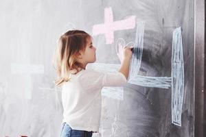 garotinha encaracolada desenhando com giz de cera na parede. obras de criança. aluno fofo escrevendo no quadro-negro foto