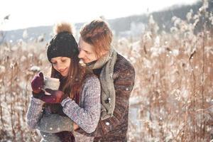 foto de um homem feliz e uma linda mulher com xícaras ao ar livre no inverno. férias e férias de inverno. casal de natal de homem e mulher feliz bebem vinho quente. Casal apaixonado