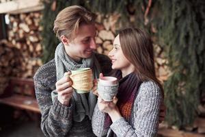 jovem casal tomando café da manhã em uma cabana romântica ao ar livre no inverno. férias e férias de inverno. casal de natal de homem e mulher feliz bebem vinho quente. Casal apaixonado foto