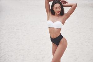 garota linda de luxo magro de biquíni na praia de areia em uma ilha tropical. corpo bronzeado sexy e figura perfeita foto