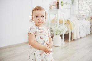 linda garotinha brincando de brinquedos. loira de olhos azuis. cadeira branca. quarto das crianças. retrato de menina feliz. conceito de infância foto