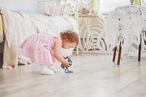 conceito de infância. menina com vestido bonito brincar com fios coloridos. quarto infantil branco vintage foto
