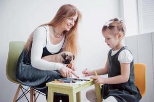 mãe e filho que a filha desenha estão engajados na criatividade no jardim de infância. pequeno pug com eles foto