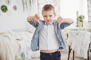 menino gesticula com o dedo para baixo. conceito de emoção. mostra sua atitude em relação às aulas e escolas foto
