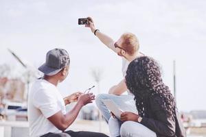 lindos amigos multi-étnicos usando um laptop na rua e fazer selphie. conceito de estilo de vida jovem foto