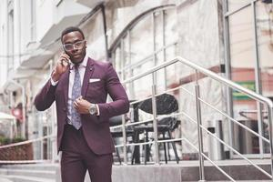 retrato de um jovem empresário afro-americano falando de terno ao telefone foto