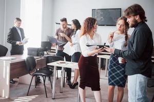 um grupo de jovens colegas fala sobre questões de trabalho em escritórios modernos. foto