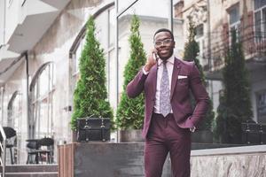 retrato de um jovem e bonito empresário afro-americano falando em um terno ao telefone. se preparando para uma reunião de negócios. foto