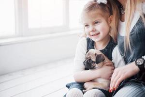 família amorosa feliz. mãe e filha menina brincando e abraçando adorável pug foto