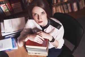 uma jovem estudante está cansada na sala de leitura da antiga biblioteca foto