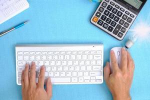 mão trabalhando computador na mesa, vista superior no espaço de trabalho com equipamento de escritório foto