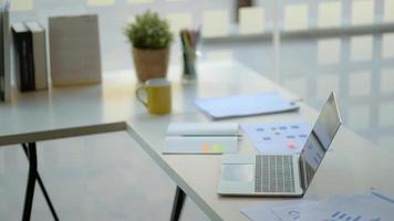 local de trabalho com laptop, material de escritório e café. foto
