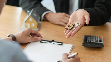 foto cortada de assinatura de um contrato de compra de casa enquanto o corretor segura a chave da casa.