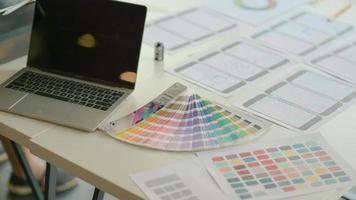 laptops com tabelas de cores e equipamentos na mesa para a equipe ux projetar aplicativos em um escritório moderno. foto
