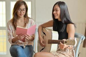 retrato de duas adolescentes tocando violão e praticando canto. foto
