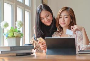 duas adolescentes estão comprando online com um tablet em casa para fazer o pedido e pagar online com cartão de crédito. foto