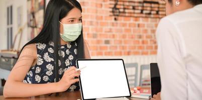 Uma corretora de seguros usando máscara está apresentando um pacote de saúde para coronavírus com um comprimido. foto