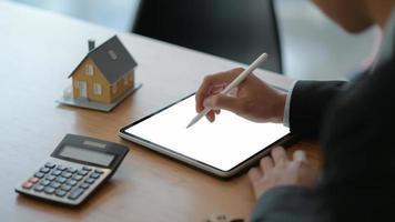 close-up de empresários usam uma caneta para escrever em um tablet com uma casa modelo e uma calculadora na mesa. foto