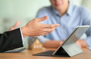 close-up de um corretor de seguros apresentando um programa de seguro saúde com seu tablet. foto