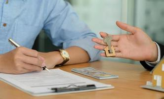 close-up de compradores de casas assinando contratos de casa e corretores segurando a chave da casa. foto