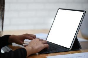 empresária trabalhando no computador tablet de tela branca com gráficos na mesa de madeira. foto