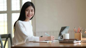 jovem aluna toma notas e usa o laptop para pesquisar pesquisas a fim de se preparar para a formatura. foto