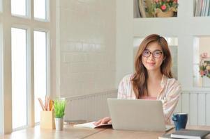 jovem empresária asiática com um laptop. ela sorriu feliz no confortável escritório. foto