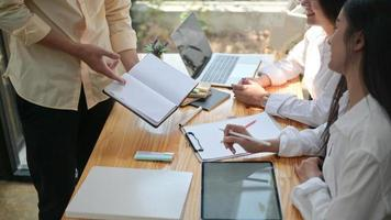 um grupo de jovens profissionais busca e forma informações para se preparar para projetos futuros. com um laptop e um notebook. foto