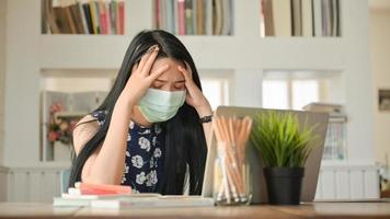 garota usando uma máscara e tocando a cabeça, ela trabalha em casa para se proteger contra o vírus covid-19. foto