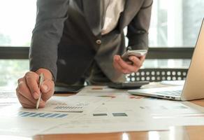empresários usam caneta, laptop e celular estão planejando um plano de marketing para melhorar a qualidade do trabalho. foto