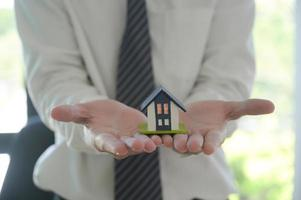 conceito de compra de casa, corretor segurando a casa modelo na mão para apresentar aos clientes. foto