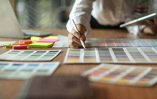 o arquiteto está comparando a cartela de cores e usando o tablet. foto