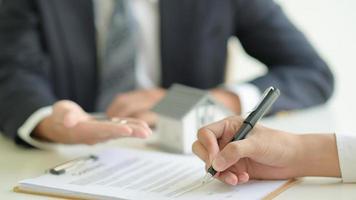 o cliente assina um contrato de empréstimo à habitação com um funcionário do banco. foto