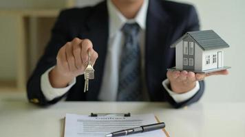 o corretor da casa tem as chaves e a casa modelo em mãos. conceito imobiliário. foto