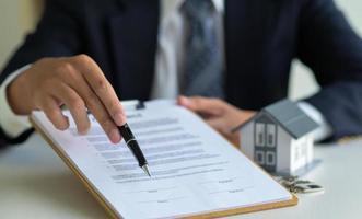 close-up do corretor da casa apontando a caneta no documento de assinatura do contrato de compra de casa. foto