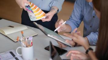uma equipe de designers profissionais usando tablets e dispositivos está discutindo ideias para criar projetos para os clientes. foto