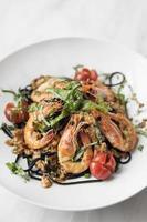 macarrão espaguete com tinta de lula preta com camarão e vegetais misturados foto