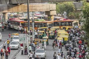 new-delhi delhi india- grande tráfego tuk tuks, ônibus e pessoas foto