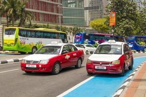 tráfego em Kuala Lumpur. veículos coloridos, carros, táxis e ônibus. foto