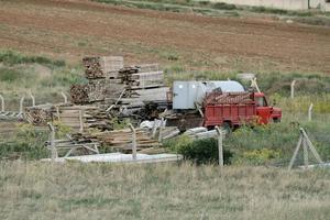 madeira armazenada, material de construção, tanque de água e um caminhão para o início da nova construção. foto