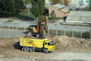 caminhões estão esperando a escavadeira preencher o solo. foto