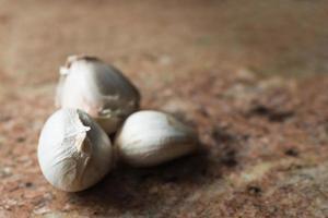três dentes de alho em uma bancada de mármore marrom. gastronomia. foto