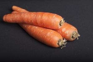 três cenouras frescas com fundo preto foto