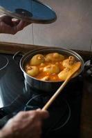 mãos de mulher envelhecida com uma panela e uma colher de pau, enquanto cozinhava batatas recheadas com atum, tomate e ovos. gastronomia em casa. prato típico asturiano foto